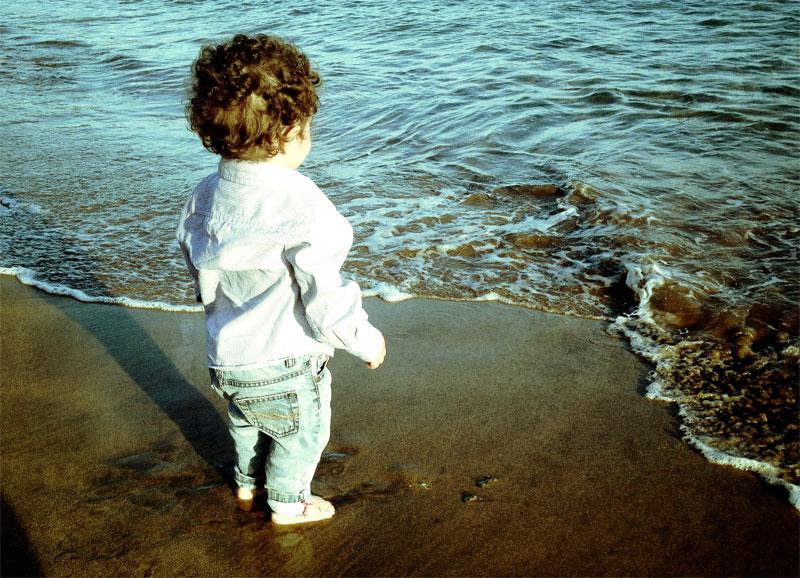 Niño vestido de domingo (para ir a misa) en la orilla de una playa