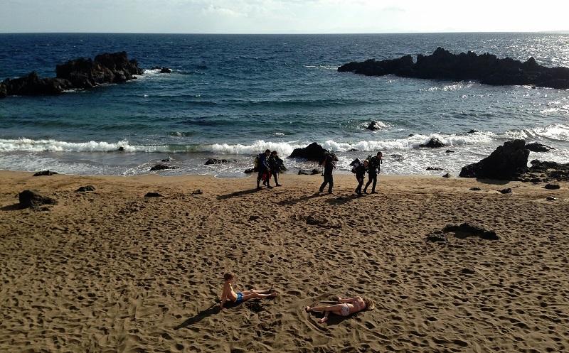 Bañistas y buzos en un día de invierno en la playa de Puerto del Carmen
