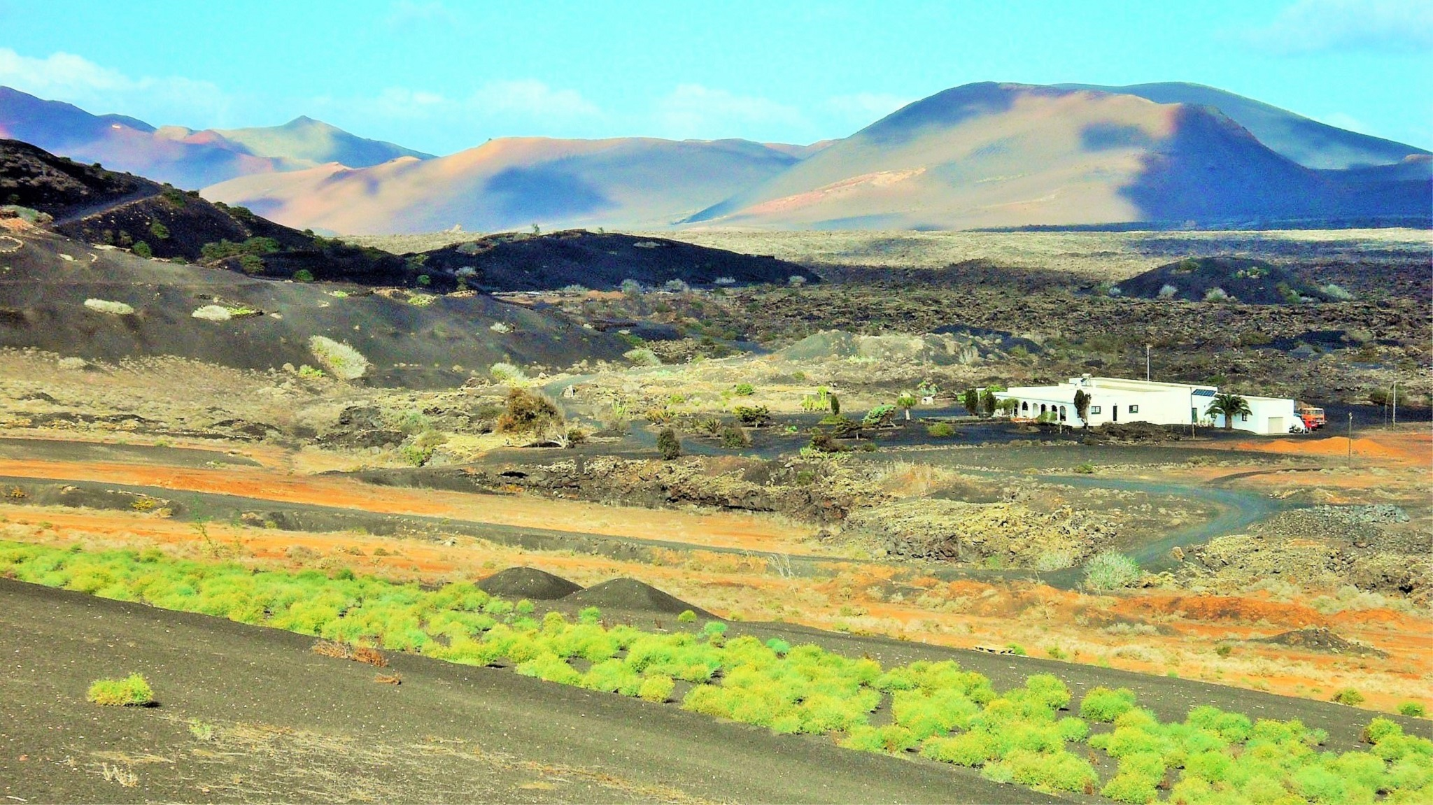 La espalda de Timanfaya, las parras y un caserón solitario