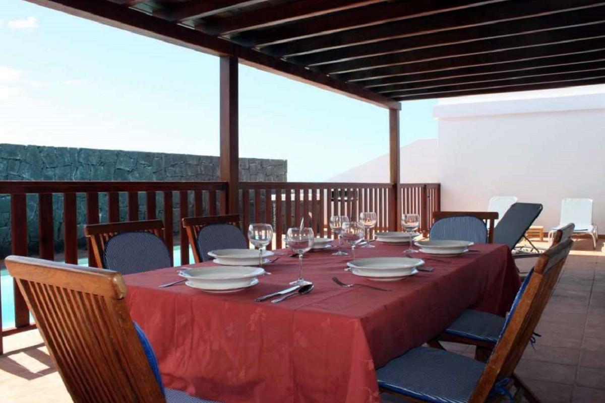 Comedor exterior bajo pérgola de madera junto a la piscina